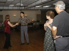 Sam and Nori Komorita of Champaign look on as David Lin, the owner and dance instructor at The Regent Ballroom in Savoy, demonstrates a salsa step with Nancy Bamnann of Lincoln, Ill. Friday night at The Regent. Lauren Lenkowski