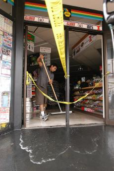 Chirag Panchal sweeps the water out of his family´s store, Hometown Pantry, on the corner of Sixth and Green streets in Champaign on Monday afternoon. Shira Weissman