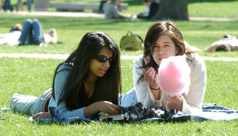 Left, Sabriya Ansari, freshman in LAS, and Jeanette Eisenberg, freshman in LAS, enjoy the weather and a stick of cotton candy after a day of classes Thursday afternoon on the Quad. Online Poster