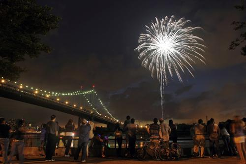 Spectators watch fireworks explode over the East River and the Triborough Bridge in this view from Astoria Park during an early Fourth of July celebration in the Queens Borough of New York, Friday, June 29, 2007. The pyrotechnic display was sponsored by C Daniel P. Derella, The Associated Press