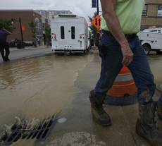 A worker walks by as Green Street is flooded following a water main broke at a construction site located at 507 E. Green St. Ryan Davis