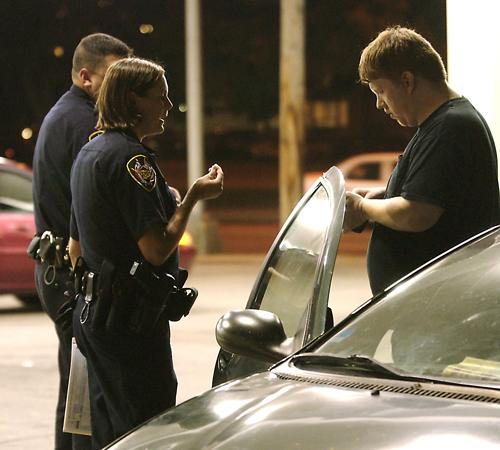 Loren Mogler, 28 of Champaign, right, is interviewed by Urbana police officers Shannon Wolfe, left center, and Rich Surles at a gas station at the intersection of Lincoln Avenue and Green Street on Wednesday night. Mogler hit a young male bicyclist, who w Erica Magda