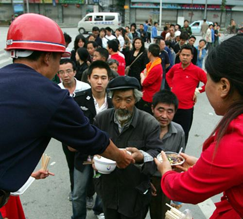 Residents line up for food handouts in a street in Dujiangyan, in Sichuan province Wednesday May 14, 2008. The official death toll from the earthquake reached almost 15,000 Wednesday, with many thousands more missing. Greg Baker, The Associated Press