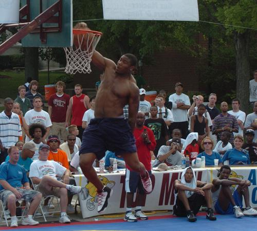 Illinois football player Jeff Cumberland throws down a dunk during the slam dunk contest at the Gus Macker 3-on-3 Tournament in Champaign on Saturday. Cumberland won the contest. Steve Contorno