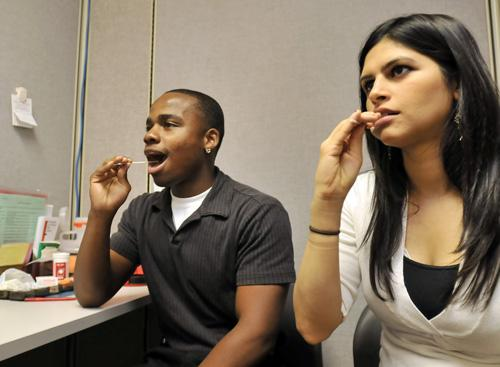 Darnell Leatherwood, left, sophomore in Business, and Zenobia Ravji, graduate student, demonstrate how to do a mouth swab to reg