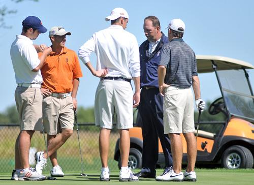 Mens golf coach Mike Small speaks with his team during practice at the University of Illinois Golf Course.