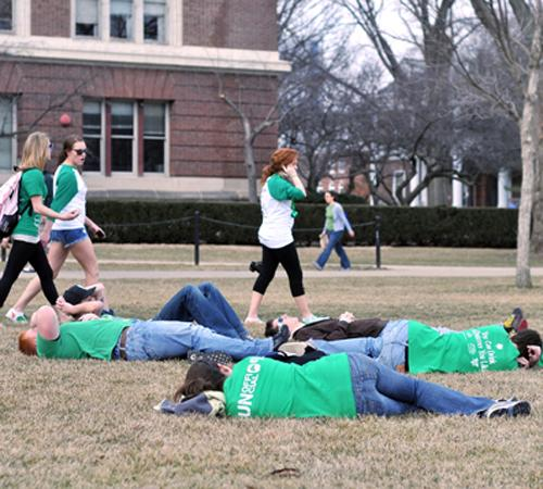 Students walk past people laying on the ground on the Quad Friday, March 6, 2009. Participants laid on the ground and pretended to nap from 11:55 to 12:05. Wesley Fane