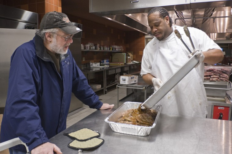 Food collector Andy Sofranko, left, watches Newman Hall cook Jermaine Cooper, right, prepare food for the St. Jude Soup Kitchen in Champaign on Tuesday, April 14.
