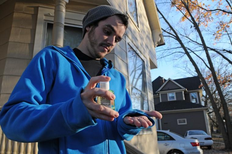 Nicholas Wagner, 09 alum, puts on hand sanitizer outside his house in Urbana on Wednesday, Nov. 11, 2009.