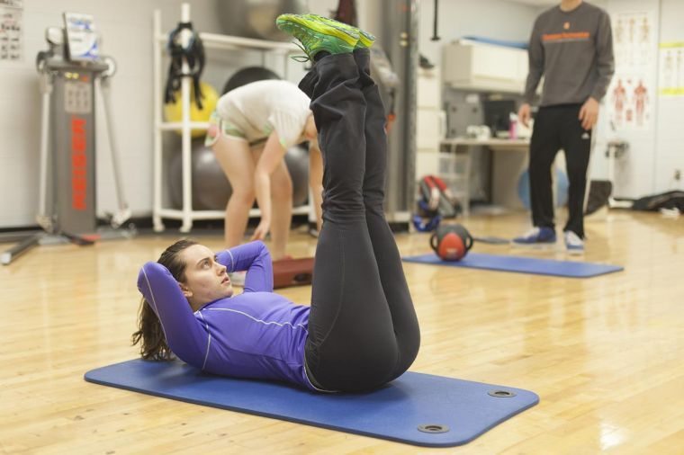 Caroline Smrokowski, sophomore in FAA, demonstrates a leg lift at the ARC on Dec. 6. She works for Campus Recreation as a personal trainer and program assistant for the personal training department.