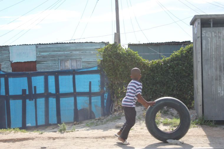 A child from Cape Flats finds enjoyment in playing with a tire.
