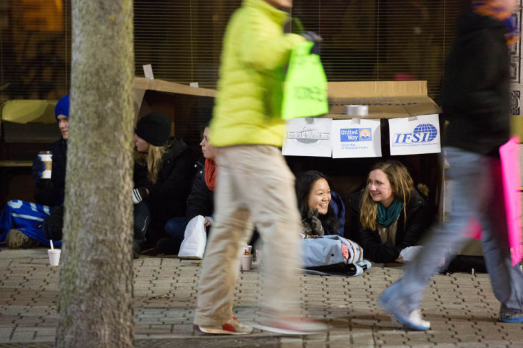 Jolie Huang and Catherine Kemp, sophomores at the University of Illinois, speak to each other in their cardboard structure for One Winter Night, which happened in downtown Champaign, on Fri., Feb. 21st.