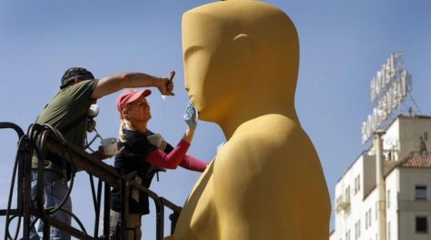 Lead scenic artist Dena D'Angelo, right, with scenic artist Rick Roberts use sand paper to prepare the giant Oscar statue for gold paint before he is loaded to the red carpet outside the Dolby Theater at Hollywood and Highland on  Feb. 25 for the Oscars which will be televised live this Sunday, March 2.