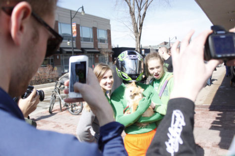 Unofficial participants pose for photos with a student who calls himself Greenman Kirby and a dog on Green St.