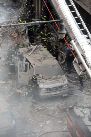 Debris covers a van as firefighters battle a blaze at the site of a possible explosion and building collapse on corner of 116th Street and Park Avenue, in the Harlem section of New York, Wednesday, March 12, 2014. (Anthony Behar/Sipa USA/MCT)