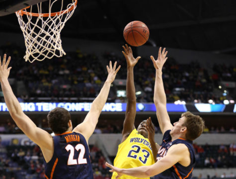 Illinois' Jon Ekey (33) and Maverick Morgan (22) attempt to block Michigan's Caris LeVert (23) during their quarter-final game of the Big Ten Men's Basketball Tournament at Banker's Life Fieldhouse, on Friday, Mar. 14, 2014 The Illini lost 64-63.