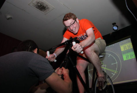 Kenny Shaevel and Michael Bodtke pedal with all their strength on stationary bikes at the Canopy Club on Wednesday night as Illini 4000 members hold on to the bikes' base to prevent shaking. All proceeds from the event will fund the nonprofit organization's annual cross-country bike ride to fight cancer.