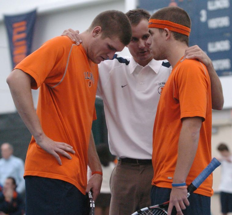 Illinois Men's Tennis Head Coach, Brad Dancer talks to juniors Ryan Rowe, left, and Brandon Davis, right, during their doubles match against Duke at Atkins Tennis Center in Urbana on Friday, February 2. Illinois beat Duke 6-1.