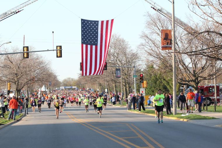 Runners+participating+in+the+Christie+Clinic+Illinois+Marathon%2C+Half+Marathon+and+10K+start+the+race+by+heading+north+on+First+Street+and+passing+under+an+American+Flag+on+Saturday%2C+April+26%2C+2014.+A+5K+race+was+held+on+Friday+night.