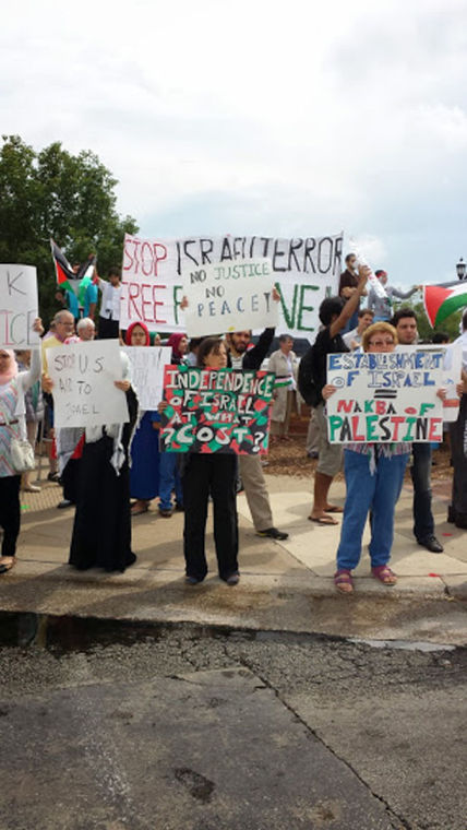 Demonstrators outside the federal courthouse in Urbana gather in a protest against Israel's offensive in Gaza on Friday. More than 150 people were in attendance.