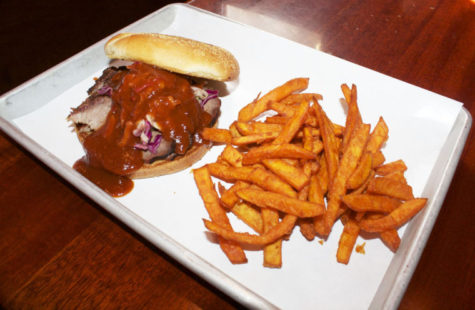 Pictured is a beef brisket sandwich covered in Georgia peach barbecue sauce and a side of sweet potato fries, served at the Black Dog Smoke and Ale House in Urbana. This barbeque joint is well-known by students and community members alike for its mouth-watering food.