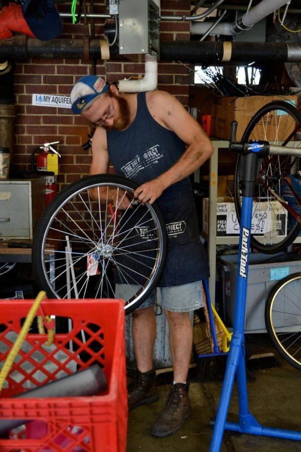 James Roedl inflates a tire at the Campus Bike Center, located at 608 E. Pennsylvania Avenue in Champaign. The project collects used bicycles and refurbishes them for further use and recently received funding to continue its work.