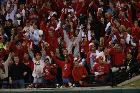 St. Louis Cardinals fans react to Matt Holliday's solo homer in the fourth inning against the Boston Red Sox during Game 5 of the World Series at Busch Stadium in St. Louis, Missouri, on Monday, October 28, 2013.