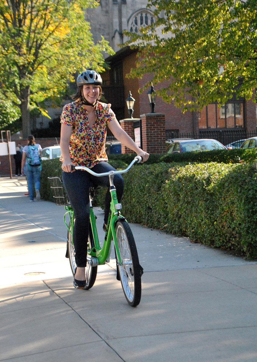 YMCA associate director, Kasey Umland, rides down the sidewalk on one of Y-Cycle's rental bikes.