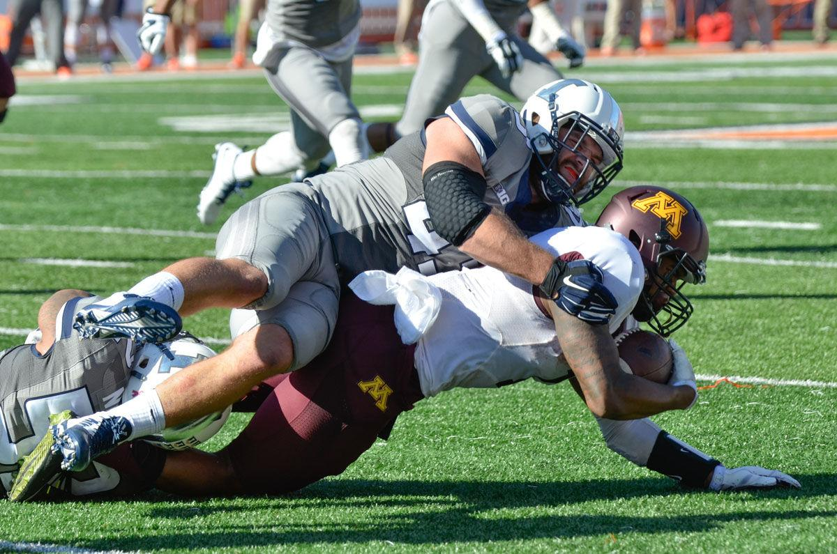 Illinois' Mason Monheim and T.J. Neal tackle Minnesota's KJ Maye during the homecoming game at Memorial Stadium on Saturday. The Illini won 28-24.
