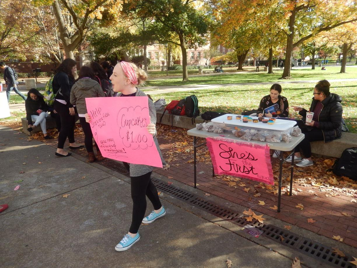 "Maggie Klinge, sophomore in social work, sells cupcakes on the Quad to raise money for ""She's the First"" on Tuesday."