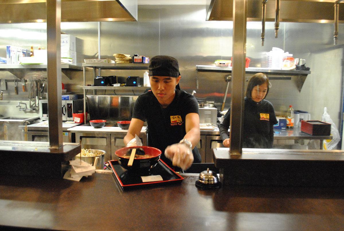 Koto Ramen employee, Calvin Law, serves a fresh bowl of ramen beside manager, Amy Chook.