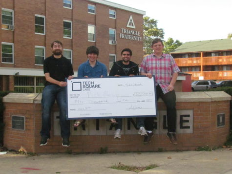 HackGT first-place winners, from left to right, Nathan Dolph, Kevin Scheer, Keagan McClelland and Kevin Jasieniecki hold a giant check in front of Triangle Fraternity that represents one of their prizes. The $50,000 on the check is an investment for the team and the future of their first-place winning software service, Pick Me Up.