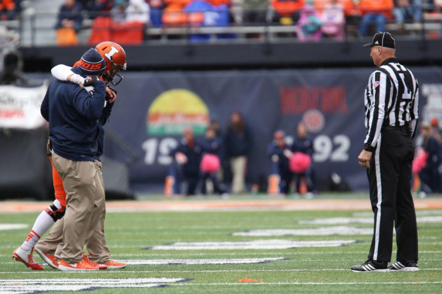 Illinois' Wes Lunt is helped off the field after he suffers an injuring during the game against Purdue at Memorial Stadium on Saturday, Oct. 4, 2014.