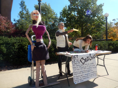 Students Georgia Christus and Chloe Peterson work next to a human-size Barbie on the Engineering Quad on Monday.