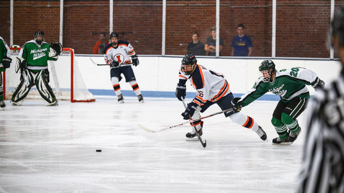 Illinois' John Olen and Michigan Sate's Michael Ferrantino clash sticks as they fight for control over the puck at the Illinois Ice Arena on Sept. 27.