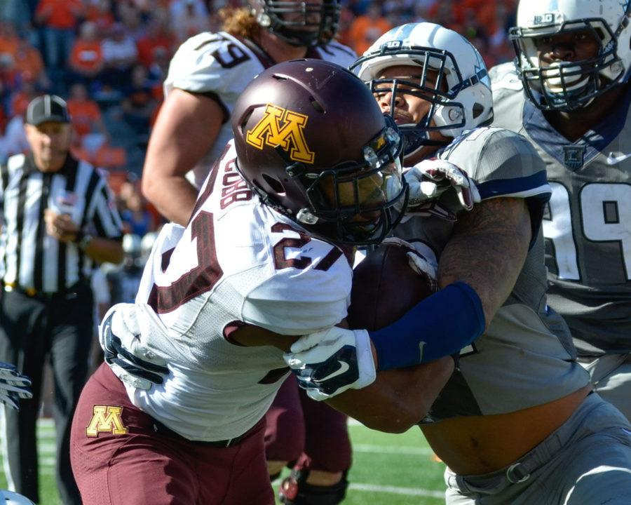 Illinois' Jarrod Clements (99) tackles Minnesota's David Cobb (27) during the homecoming game at Memorial Stadium on Saturday. The Illini won 28-24.