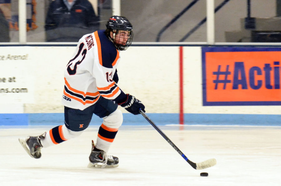 Illinois' James Mcging manuevers the puck down the rink during the hockey game against Aurora University at the Ice Arena on Friday.