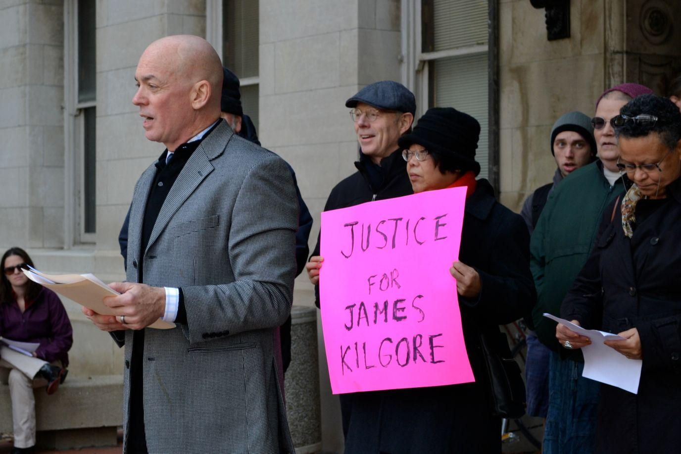 Dr. William Sullivan of the Department of Landscape Architecture gathers with fellow supporters of James Kilgore to speak with reporters outside the Henry Administration Building on Monday morning.