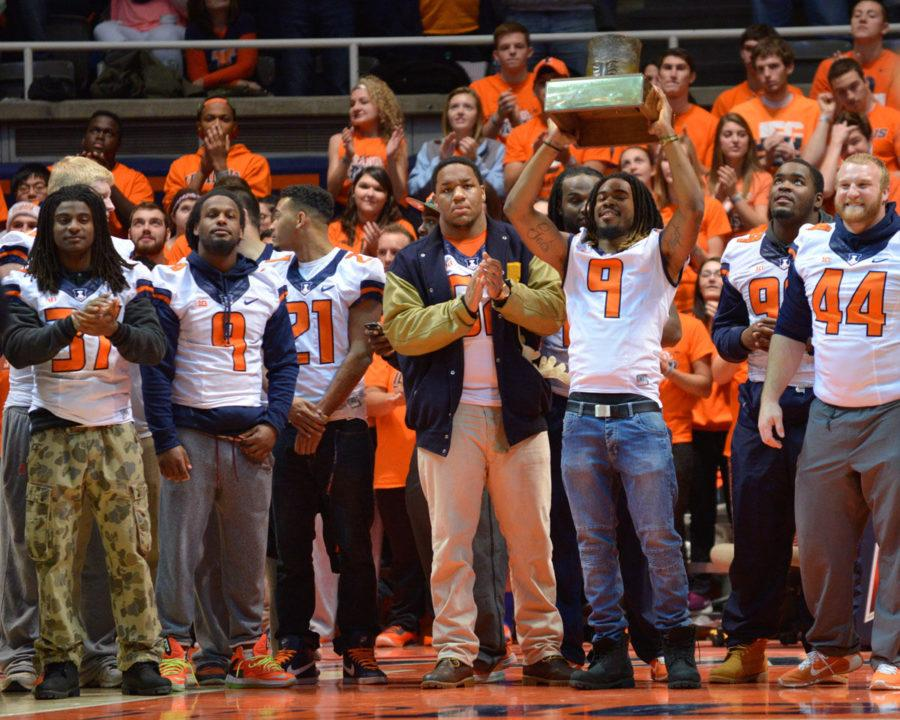 The+Illini+football+team+presents+the+Land+of+Lincoln+trophy+during+the+basketball+game+against+American+on+Saturday.+The+Illini+won+the+trophy+by+beating+Northwestern.