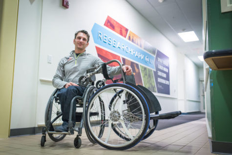Josh George, graduate of the College of Media and founding partner of Intelliwheels, poses beside an early prototype he constructed.