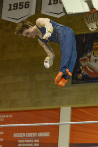 Illinois' Tyson Bull performs a high bar routine at the Orange and Blue Exhibition at Huff Hall on Sunday.