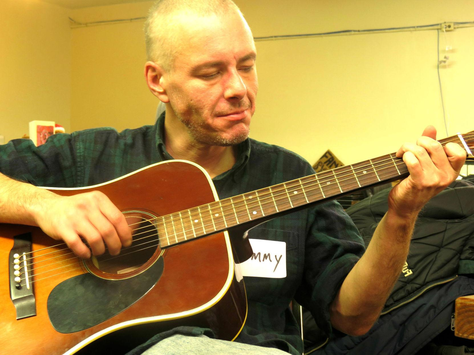 Tommy, a guest at The Phoenix, strums his guitar in the recreation room of the drop-in center on Dec. 16.