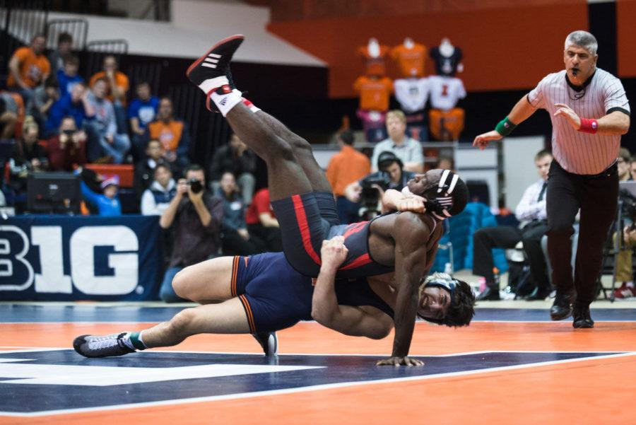 Illinois' Isaiah Martinez slams his opponent to the ground during the match versus Nebraska at Huff Hall on Friday. The Illini lost 22-9 and were 1-1 on the weekend.