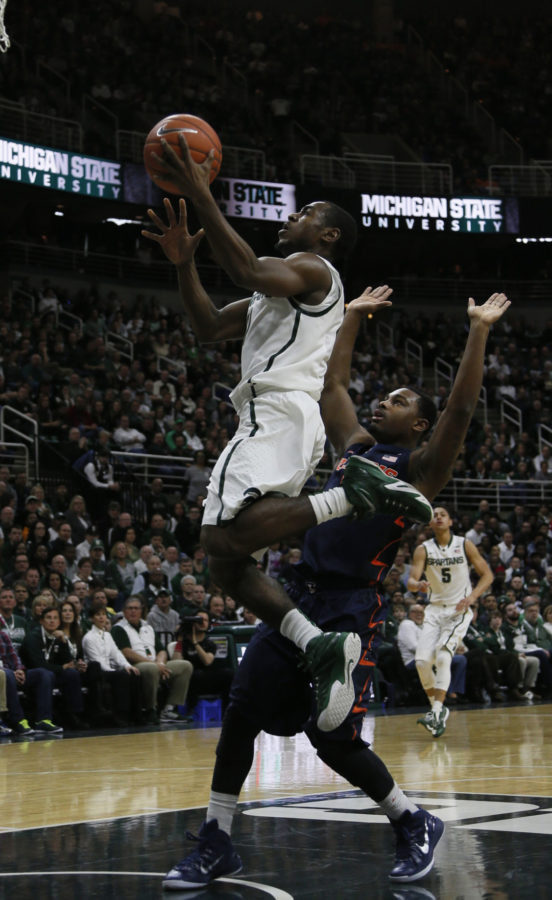 Michigan State's Lourawls Nairn Jr. drives by Illinois' Ahmad Starks for a score in the first half on Saturday at the Breslin Center in East Lansing, Mich. The Illini won, 59-54.