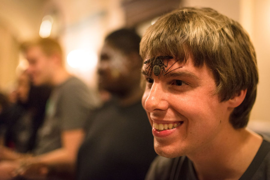 Tyler Hedlund, graduate in LAS, smiles as he introduces the whipspider on his face to curious spectators at Foellinger Auditorium on Friday.