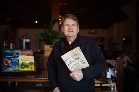 Allen Strong, the owner of The Courier Cafe, is holding the old newspapers in the cafe at March 20.