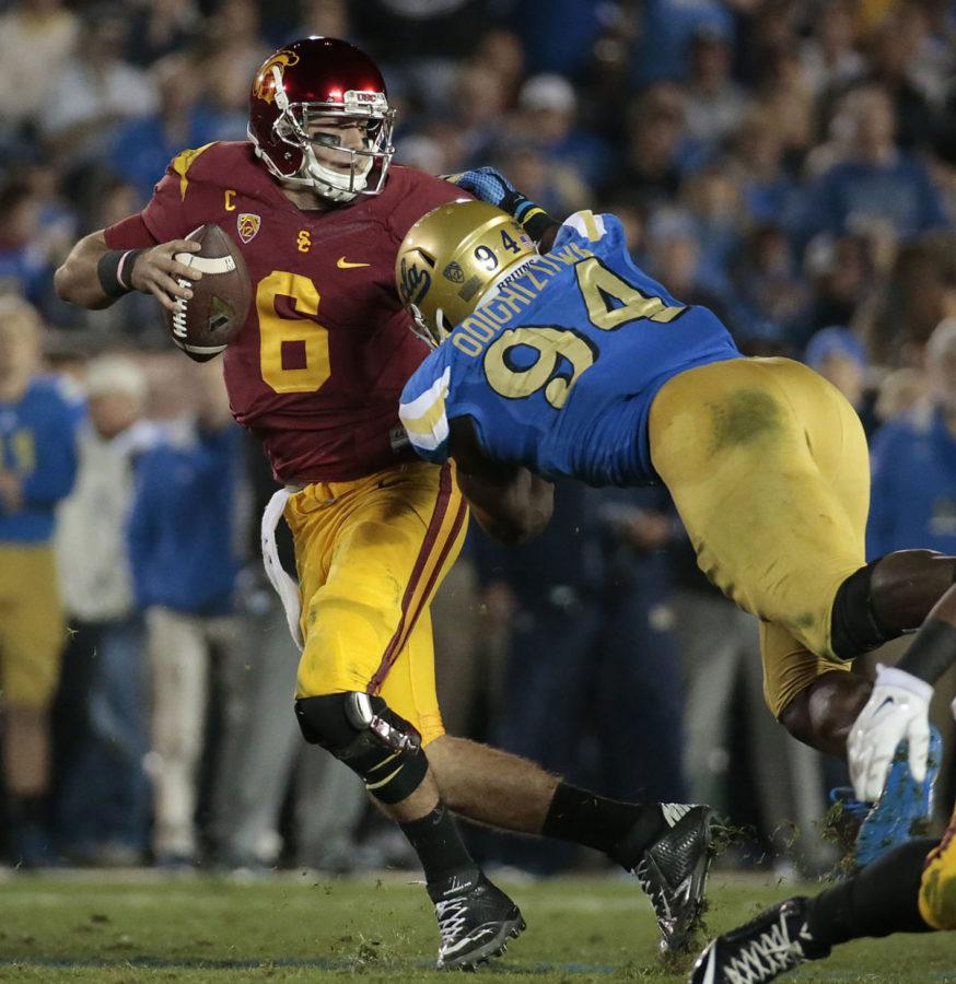 USC quarterback Cody Kessler (6) escapes the grasp of UCLA defensive lineman Owamagbe Odighizuwa in the second half on Saturday, Nov. 22, 2014, at the Rose Bowl in Pasadena, Calif. UCLA won, 38-20. (Luis Sinco/Los Angeles Times/TNS)