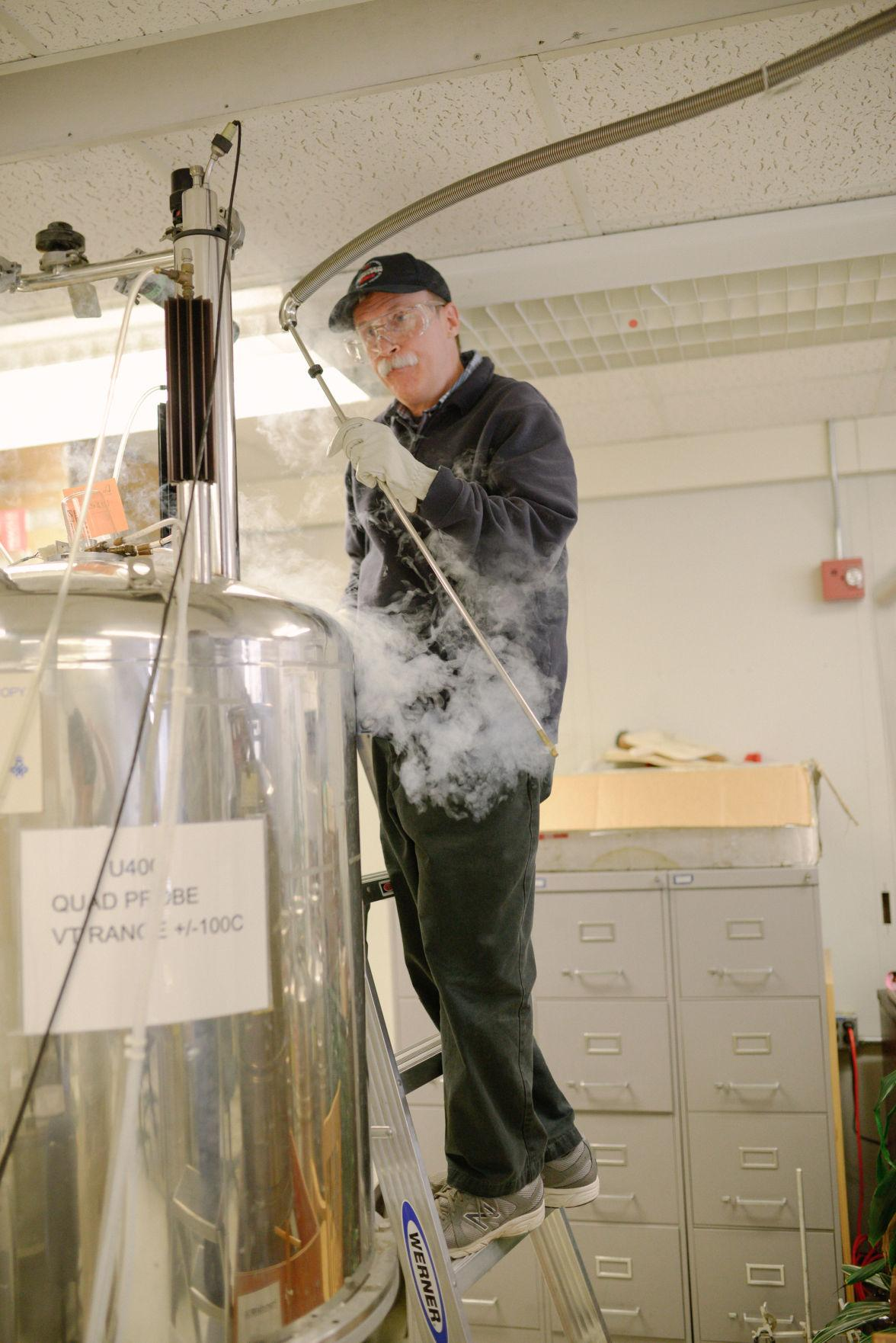 Dean Olson, Director of the Nuclear Magnetic Resonance (NMR) Lab, prepares to insert a liquid helium filler into a superconducting magnet apparatus at the Chemical and Life Sciences Laboratory A on February 10.