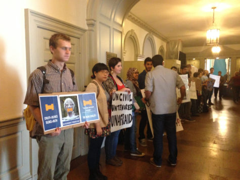 Student activists stand at the back of the Illini Union Ballroom, protesting the rejection of Salaita and censorship.