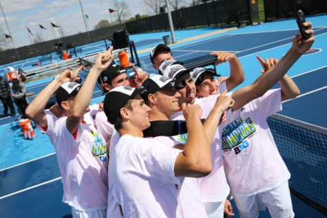 The Fighting Illini men's tennis team take a picture together as champions after the Big Ten Men's Tennis Tournament final against Ohio State at the Khan Outdoor Tennis Complex, on Sunday. The Illini won 4-0.